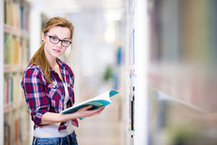 Pretty, female college student in a library, looking for a book Royalty Free Stock Photography