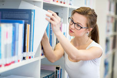 Pretty, female college student in a library, looking for a book Stock Photo