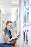 Pretty, female college student in a library, looking for a book Stock Image