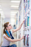 Pretty, female college student in a library. Looking for a book (shallow DOF; color toned image Stock Photo