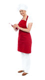 Pretty female cook writing recipe on notepad Stock Images