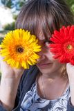 Pretty female  covering her eyes with fresh colorful flowers and enjoying spring time Royalty Free Stock Photo