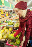 Pretty female customer buying melon Stock Photo