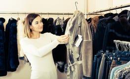 Pretty female customer examining sheepskin coat Royalty Free Stock Photography