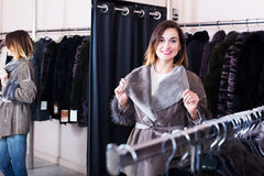 Pretty female customer examining sheepskin coat Stock Photography