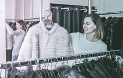 Pretty female customer examining sheepskin coat Royalty Free Stock Image