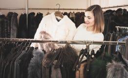 Pretty female customer examining sheepskin coat Royalty Free Stock Images