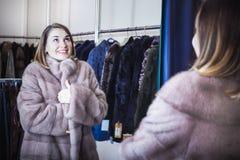 Pretty female customer examining sheepskin coat Stock Image