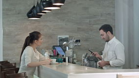 Pretty female customer giving her phone number to handsome barista stock footage