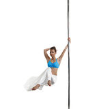 Pretty female dancer spinning on pole in studio Stock Photo