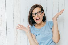 Pretty female with dark hair, pleasant appearance, looks joyfully at camera, keeps palms raised, gestures happily, wears casual t. Shirt and spectacles, stands stock photo