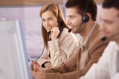 Pretty female dispatcher in call center smiling. Pretty female dispatcher working in callcenter smiling Royalty Free Stock Photo