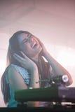 Pretty female DJ having fun while listening music on headphone Royalty Free Stock Photography