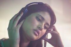 Pretty female DJ listening music on headphone Royalty Free Stock Image