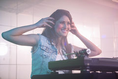 Pretty female DJ listening to the headphone while playing music Stock Images