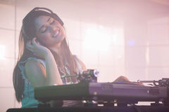 Pretty female DJ listening to the headphone while playing music Stock Image
