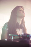Pretty female DJ looking at audience while playing music Royalty Free Stock Image