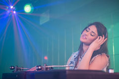 Pretty female DJ playing music Stock Photography