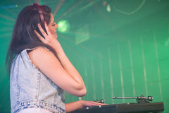 Pretty female DJ playing music Stock Images