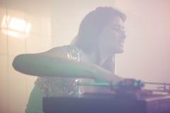 Pretty female DJ playing music Stock Image