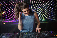 Pretty female DJ playing music. At the nightclub Royalty Free Stock Photography