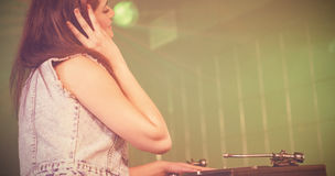 Pretty female DJ playing music. At nightclub Stock Photography