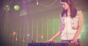 Pretty female DJ playing music. At the nightclub Royalty Free Stock Images