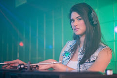 Pretty female DJ playing music. Portrait of pretty female DJ playing music at the nightclub Royalty Free Stock Images