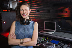 Pretty female DJ standing with arms crossed Royalty Free Stock Image