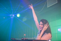 Pretty female DJ waving her hand while playing music Royalty Free Stock Photography
