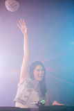 Pretty female DJ waving her hand while playing music. At nightclub Royalty Free Stock Photos