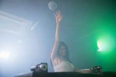 Pretty female DJ waving her hand while playing music Stock Photo
