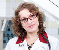 Pretty female doctor in glasses with stethoscope. Pretty female doctor with curly hair in glasses with stethoscope Royalty Free Stock Image