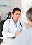 Pretty female doctor listening Royalty Free Stock Images