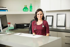 Pretty female doctor sitting at her desk Stock Image