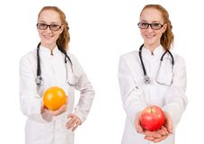 Pretty female doctor with stethoscope and orange isolated on whi Stock Photos