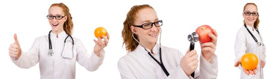 Pretty female doctor with stethoscope and orange isolated on whi Royalty Free Stock Photography