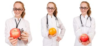 Pretty female doctor with stethoscope and orange isolated on whi Royalty Free Stock Image