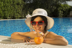 Pretty female drinking grapefruit juice at the edge of a swimming pool Royalty Free Stock Photo