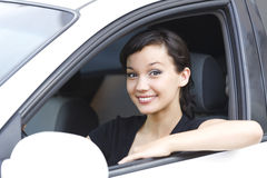 Pretty female driver. In a white car during test drive Royalty Free Stock Photos