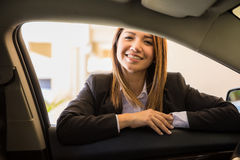 Pretty female driver ready for a trip. Gorgeous young female driver in a suit leaning on a car door and ready to drive you to your next destination stock photos
