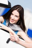 Pretty female driver showing the cabriolet key. Pretty female driver in a car showing the car key Stock Photos