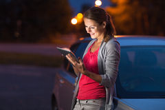 Pretty, female driver using her tablet computer. (shallow DOF; color toned image Royalty Free Stock Photos