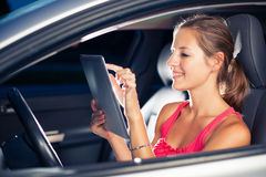 Pretty, female driver using her tablet computer. (shallow DOF; color toned image Stock Photos