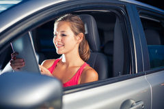 Pretty, female driver using her tablet computer Royalty Free Stock Image