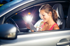 Pretty, female driver using her tablet computer. (shallow DOF; color toned image Stock Images