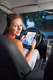 Pretty, female driver using her tablet computer Stock Photo