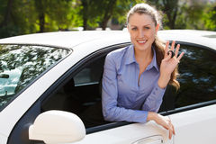 Pretty female driver. In a white car showing the car key Stock Photography
