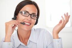 Pretty female employee talking on headphones Royalty Free Stock Photos