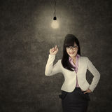 Pretty female entrepreneur and bright lamp Stock Photography